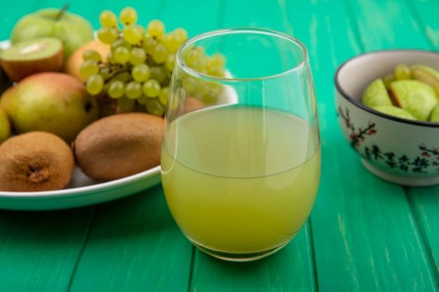 Vooraanzicht frisdrank in een glas met groene appels kiwi groene druiven en peer op een plaat op een groene achtergrond Gratis Foto
