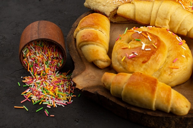 Vooraanzicht gebak samen met croissants op het bruine bureau samen met kleurrijke snoepjes in het donker Gratis Foto