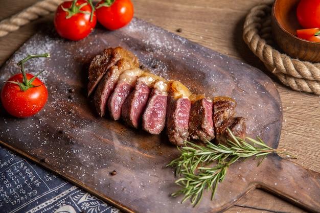 Vooraanzicht gebakken gesneden vlees met greens en verse rode tomaten op houten bureau Gratis Foto
