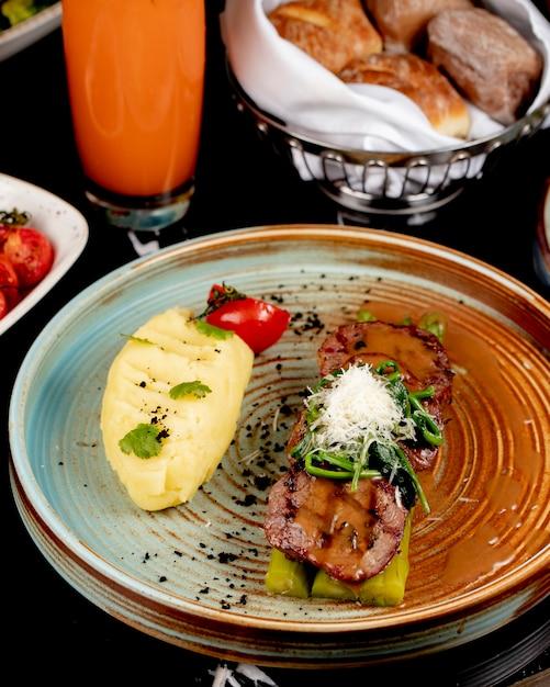Vooraanzicht gebakken vlees op asperges met aardappelpuree en kruiden in een plaat Gratis Foto