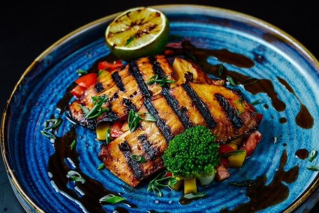 Vooraanzicht gegrild visfilet met groenten en een schijfje citroen op een plaat Gratis Foto