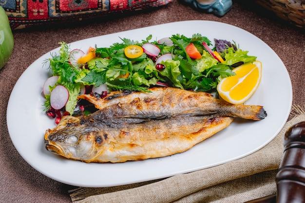Vooraanzicht gegrilde vis met een salade van groenten en kruiden met een schijfje citroen Gratis Foto
