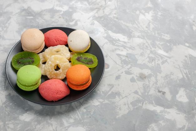 Vooraanzicht gekleurde kleine cakes met gedroogde ananasringen op lichtwit bureau Gratis Foto