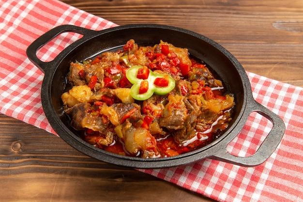 Vooraanzicht gekookte groentemaaltijd inclusief groenten en vlees binnen op bruin bureau Gratis Foto