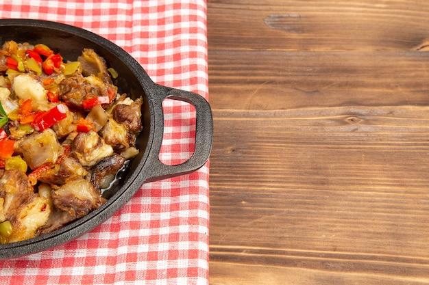 Vooraanzicht gekookte groentemaaltijd inclusief groenten en vlees binnen op houten bruin bureau Gratis Foto