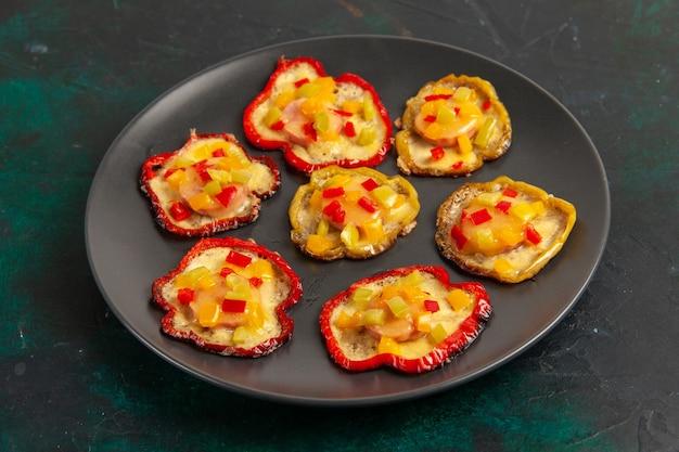 Vooraanzicht gekookte paprika's voor lunch in plaat op donkere ondergrond Gratis Foto