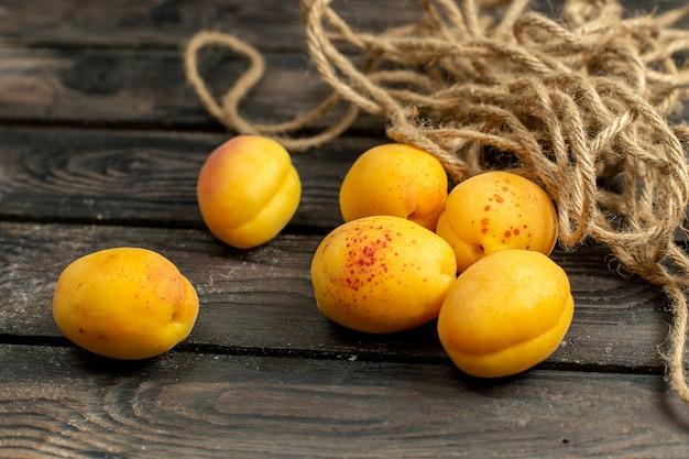 Vooraanzicht gele abrikozen zacht en vers fruit op de bruine rustieke achtergrond fruit vitamine zomer Gratis Foto