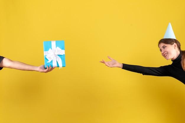 Vooraanzicht gelukkig schattig meisje met feestmuts proberen te bereiken geschenkdoos Gratis Foto