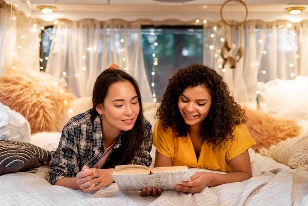 Vooraanzicht gelukkige vrouwenvrienden lezen Gratis Foto