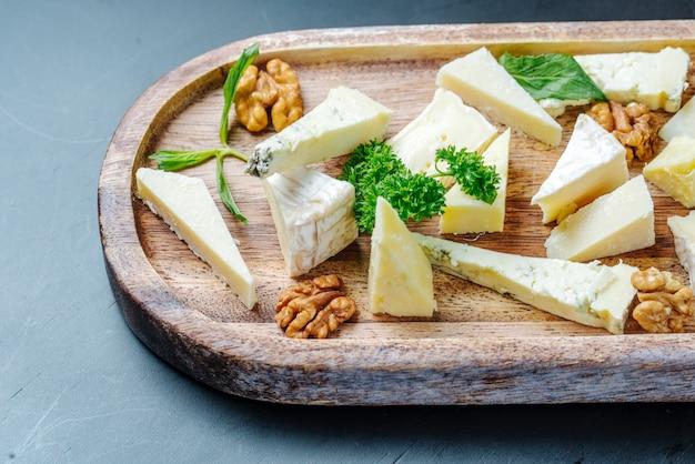 Vooraanzicht gesneden roquefort kaas met groenen en noten op een houten plaat Gratis Foto