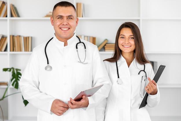 Vooraanzicht glimlachende mannelijke en vrouwelijke arts Gratis Foto