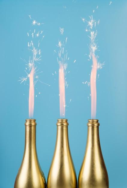 Vooraanzicht gouden flessen met vuurwerk Gratis Foto