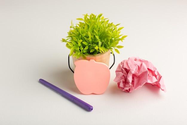 Vooraanzicht groene plant met sticker en pen op wit oppervlak Gratis Foto