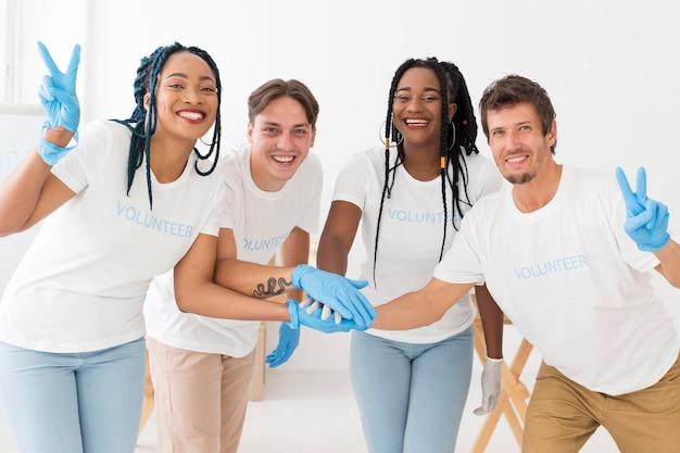 Vooraanzicht groep vrijwilligers hand in hand Gratis Foto