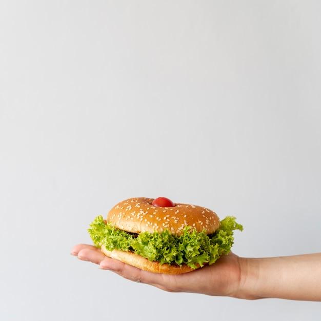 Vooraanzicht hamburger gehouden door persoon Gratis Foto