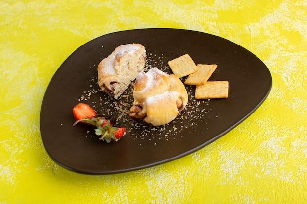 Vooraanzicht heerlijk gebak binnen plaat met crackers op de gele tafel, bak zoete thee fruit gebak Gratis Foto