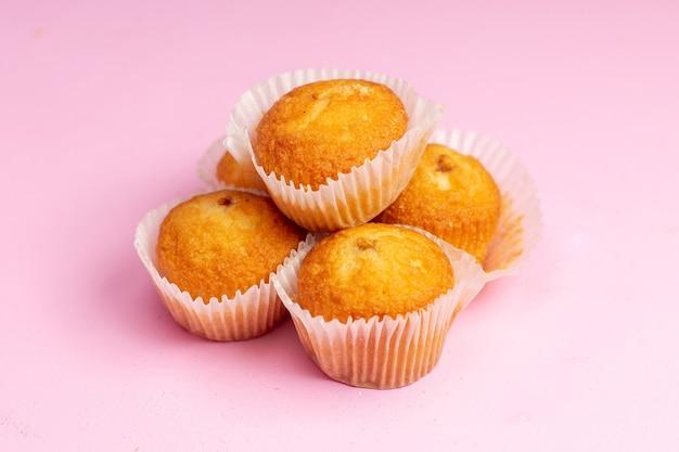 Vooraanzicht heerlijke kleine cakes met fruitvulling op de roze achtergrond cake koekje koekje zoete suiker thee Gratis Foto
