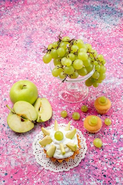 Vooraanzicht in de verte verse groene druiven, geheel zuur en heerlijk fruit met kleine cakes op licht Gratis Foto