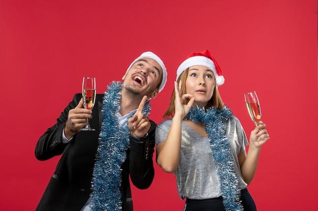 Vooraanzicht jong koppel nieuwjaar vieren op rode muur liefde kerstfeest drankje Gratis Foto