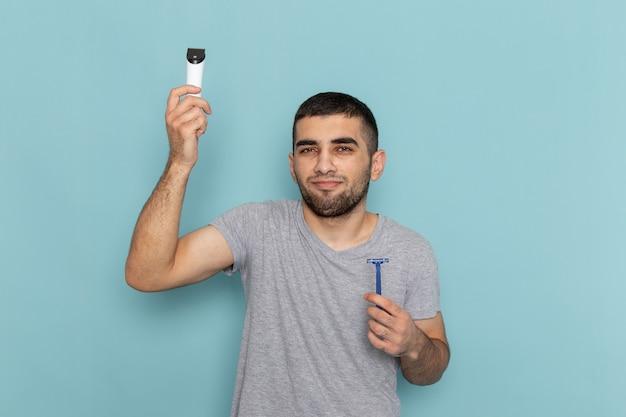 Vooraanzicht jong mannetje in grijs t-shirt met scheermes en elektrisch scheerapparaat op het blauw Gratis Foto
