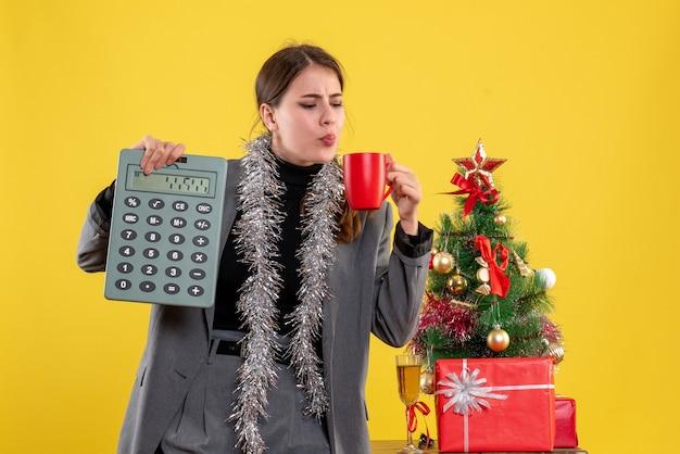 Vooraanzicht jong meisje bedrijf rekenmachine en een kopje koffie in de buurt van kerstboom en geschenken cocktail Gratis Foto