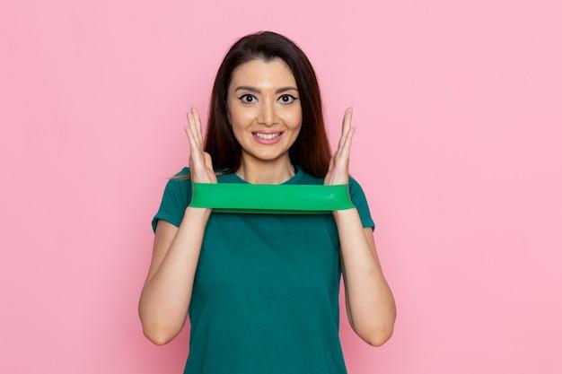 Vooraanzicht jong wijfje die groen verband houden en op lichtroze muuroefening sport training atleet schoonheid glimlachen Gratis Foto