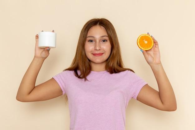 Vooraanzicht jonge aantrekkelijke vrouw in roze t-shirt en spijkerbroek met sinaasappel Gratis Foto