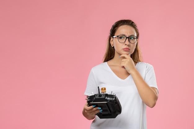 Vooraanzicht jonge aantrekkelijke vrouw in wit t-shirt met afstandsbediening met denken uitdrukking op de roze achtergrond Gratis Foto