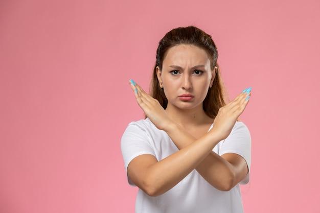 Vooraanzicht jonge aantrekkelijke vrouw in wit t-shirt met verbod bord met ontevreden uitdrukking op de roze achtergrond Gratis Foto