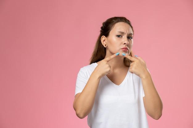 Vooraanzicht jonge aantrekkelijke vrouw in wit t-shirt wat betreft haar gezicht op de roze achtergrond Gratis Foto
