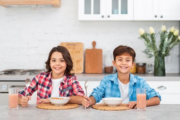 Vooraanzicht jonge broers en zussen samen eten van ontbijt Gratis Foto