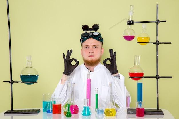 Vooraanzicht jonge chemicus houdt van zijn laatste chemische tests in een laboratorium Gratis Foto