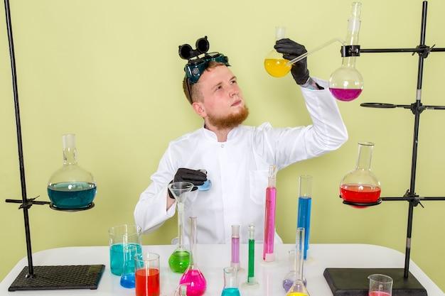 Vooraanzicht jonge chemicus onderzoek naar gele chemische stof in een laboratorium Gratis Foto