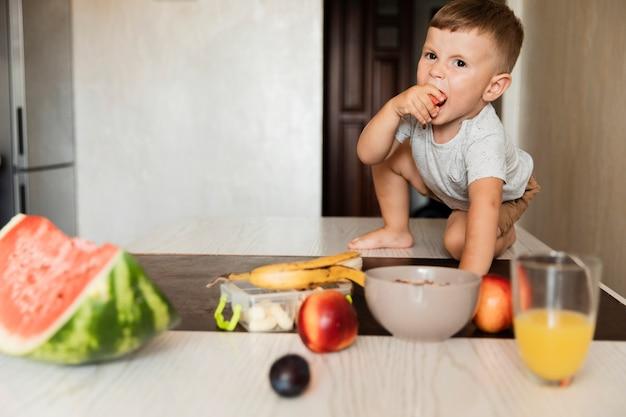 Vooraanzicht jonge jongen die fruit eet Gratis Foto