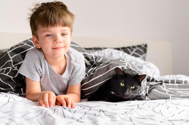 Vooraanzicht jonge jongen met zijn kat thuis Gratis Foto