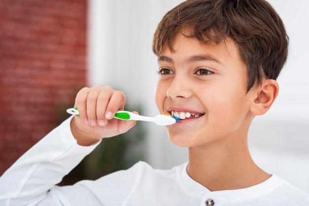 Vooraanzicht jonge jongen poetsen theets Gratis Foto