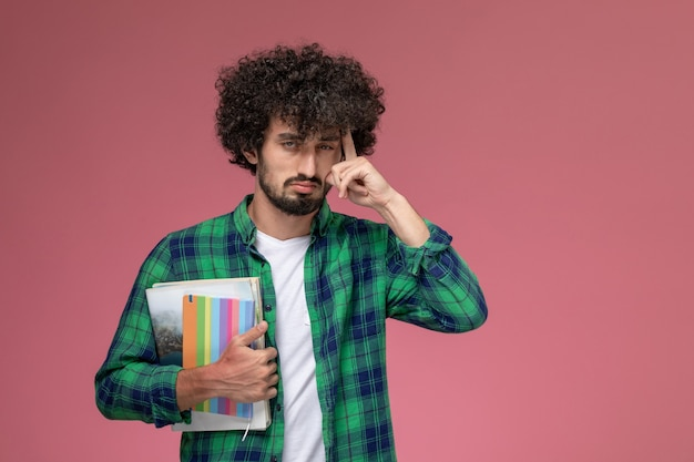 Vooraanzicht jonge kerel die over iets met notitieboekjes nadenkt Gratis Foto