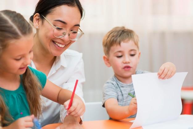 Vooraanzicht jonge leraar helpt haar studenten in de klas Gratis Foto