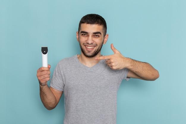 Vooraanzicht jonge man in grijs t-shirt met elektrisch scheerapparaat op het blauwe scheren baard mannelijke haarschuim Gratis Foto