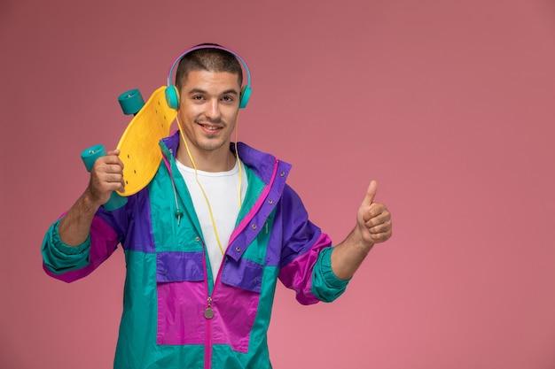 Vooraanzicht jonge man in kleurrijke jas luisteren naar muziek met skateboard op het roze bureau mannetje Gratis Foto