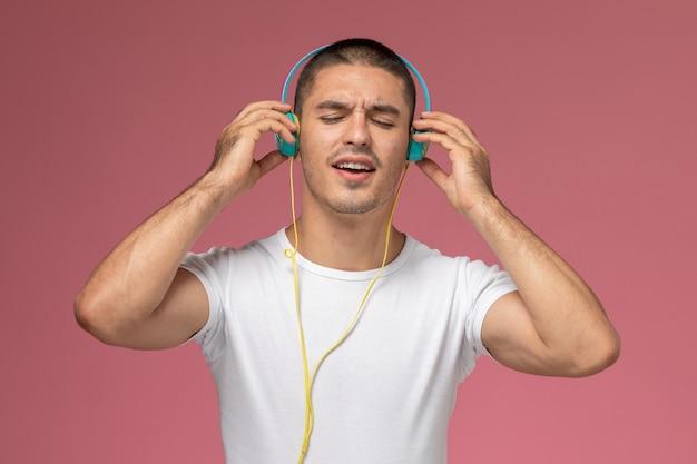 Vooraanzicht jonge man in wit t-shirt luisteren naar muziek via koptelefoon op de roze achtergrond Gratis Foto