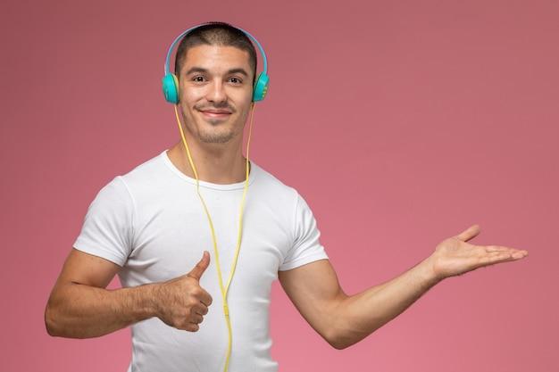 Vooraanzicht jonge man in wit t-shirt luisteren naar muziek via zijn koptelefoon lachend op lichtroze achtergrond Gratis Foto