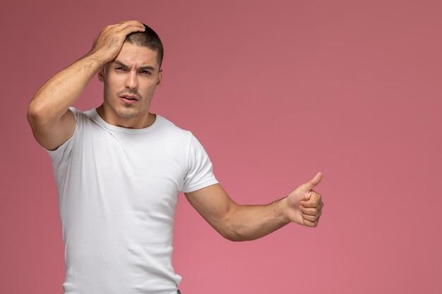 Vooraanzicht jonge man in wit t-shirt met zijn hoofd op roze achtergrond Gratis Foto
