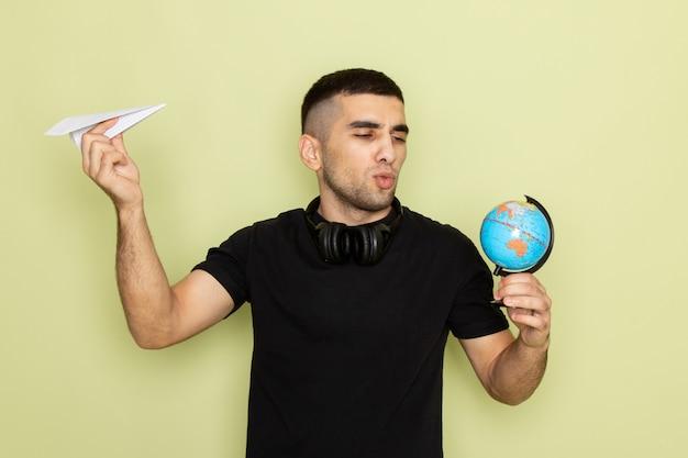Vooraanzicht jonge man in zwart t-shirt met papieren vliegtuigje en kleine wereldbol op groen Gratis Foto
