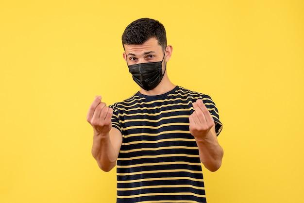 Vooraanzicht jonge man in zwart-wit gestreept t-shirt geld verdienen ondertekenen met vinger op gele geïsoleerde achtergrond Gratis Foto