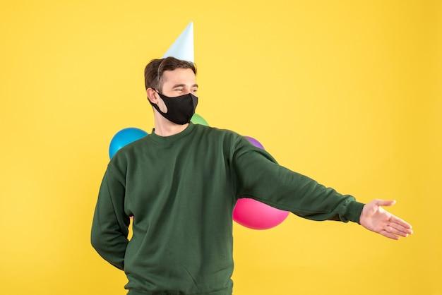 Vooraanzicht jonge man met feestmuts en kleurrijke ballonnen hand geven staande op geel Gratis Foto