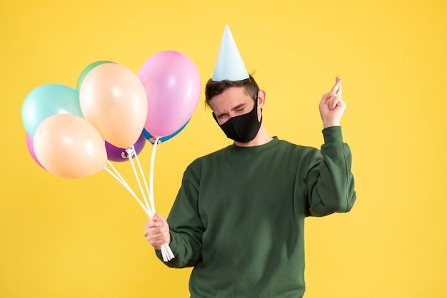 Vooraanzicht jonge man met feestmuts en kleurrijke ballonnen maken geluk teken staande op geel Gratis Foto