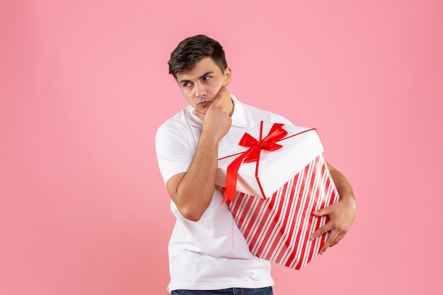 Vooraanzicht jonge man met grote kerstcadeau denken op roze achtergrond Gratis Foto