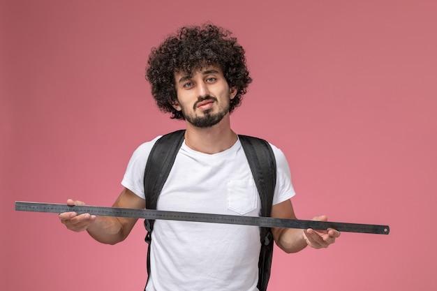 Vooraanzicht jonge man met liniaal voor onderwijs Gratis Foto