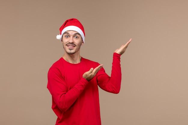 Vooraanzicht jonge man poseren met opgewonden gezicht op bruine achtergrond emoties vakantie kerst Gratis Foto